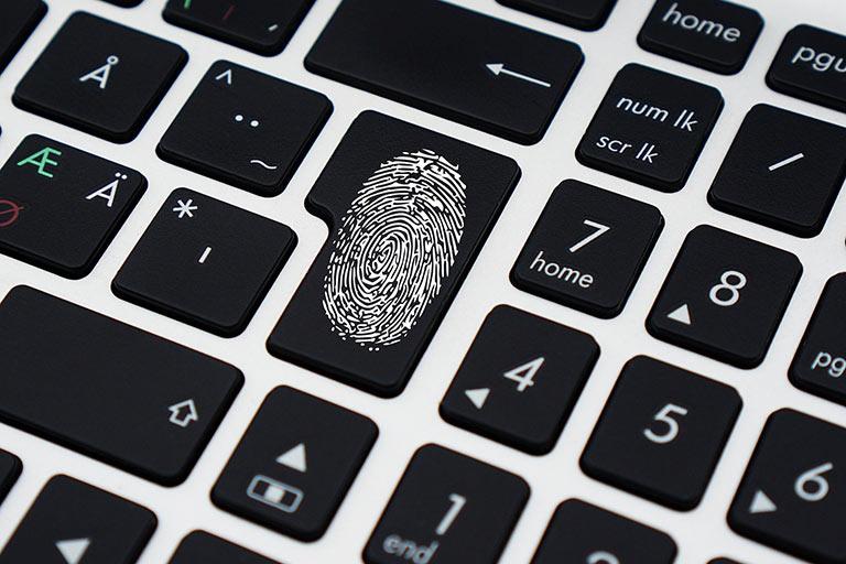 Close up of a laptop keyboard with fingerprint on Enter key