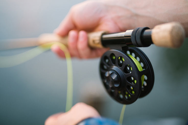 Close up of a person fly fishing