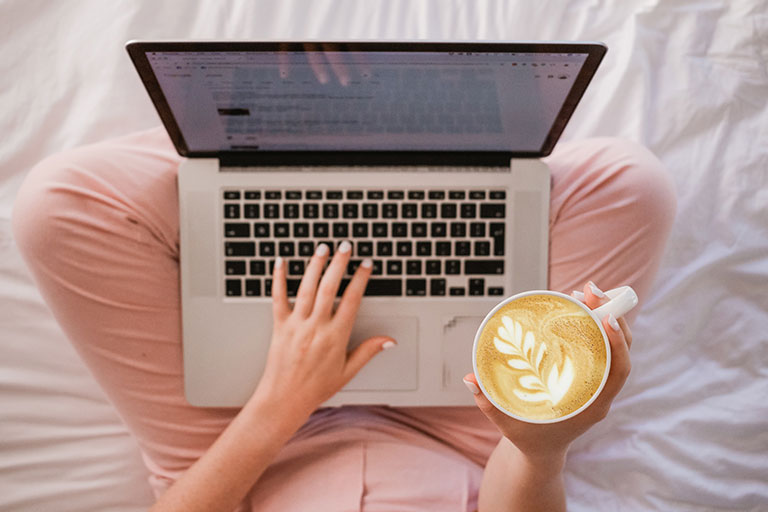 Person using laptop on bed with coffee