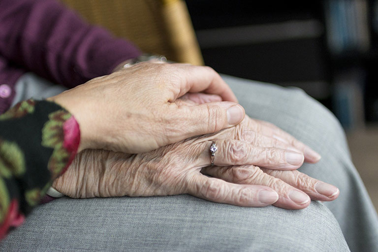 Carer holding elderly person's hand