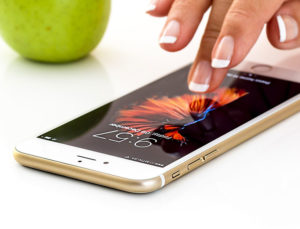 Hand touching screen of Apple phone