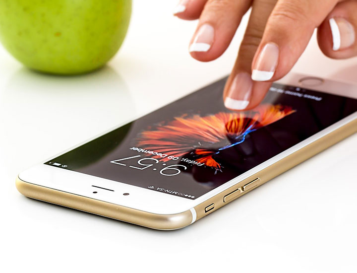 Hand touching screen of Apple phone