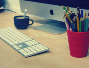 Mac and keyboard on desk with coffee and pencil cup